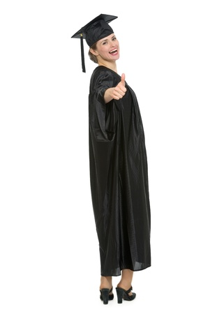 Full length portrait of graduation student woman showing thumbs up.  photo