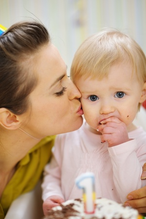 Mother kissing baby eating birthday cake Stock Photo - 13407719