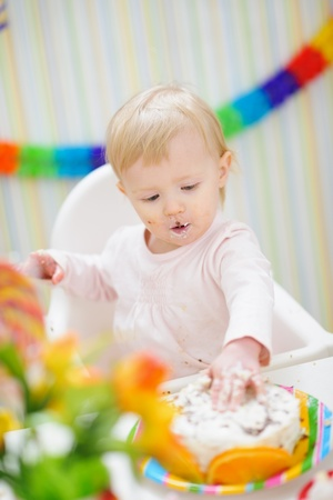 eat smeared baby: Eat smeared baby touching birthday cake Stock Photo
