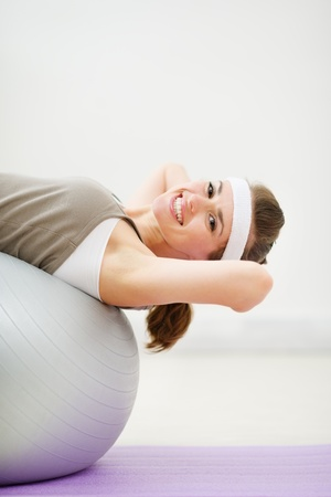Happy woman doing abdominal crunch on fitness ball