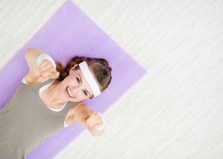 Smiling woman laying on fitness mat and pointing on you photo