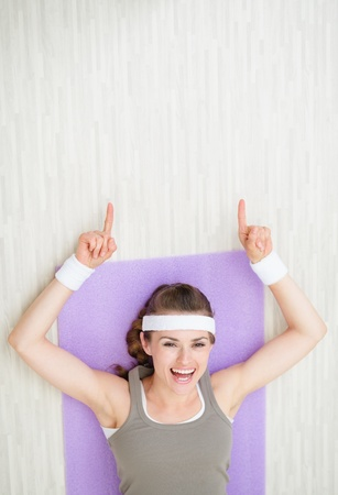 Happy young woman laying on fitness mat and pointing on copy space photo