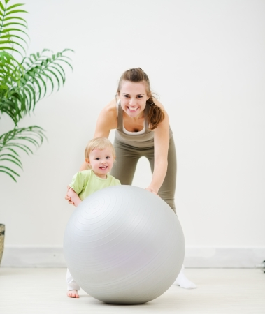 Portrait of mother and baby playing with fitness ball photo