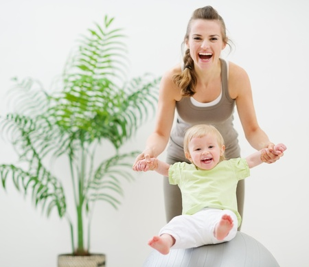 Mother and baby playing with fitness ball Stock Photo