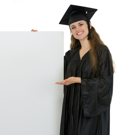 Smiling graduation student woman showing on blank billboard Stock Photo - 13523721
