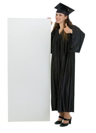 Graduation student holding blank billboard and showing thumbs up photo