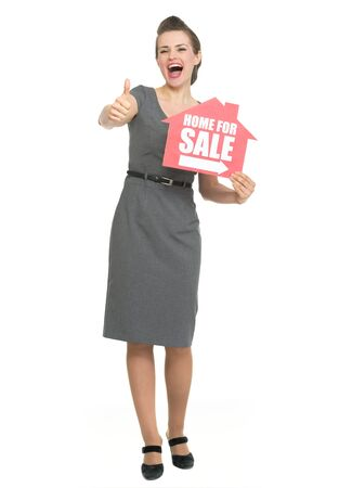 Smiling realtor showing thumbs up and home for sale sign photo