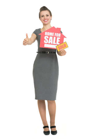Smiling realtor showing thumbs up and home for sale sold sign Stock Photo - 13611528