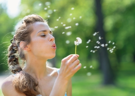 Young woman blowing away dandelion photo