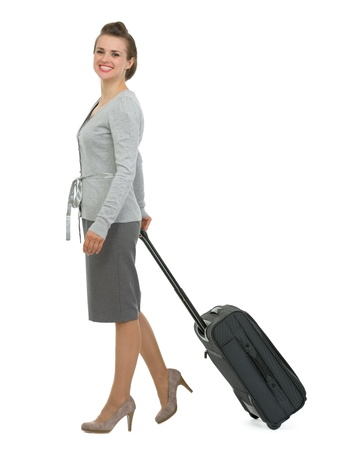 Happy traveling woman with suitcase walking sideways Stock Photo - 13611520
