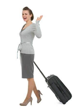 Happy traveling woman with suitcase waving hand Stock Photo - 13611524