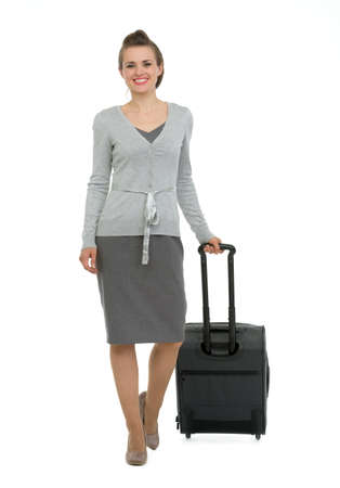 Happy traveling woman with suitcase making step forward photo
