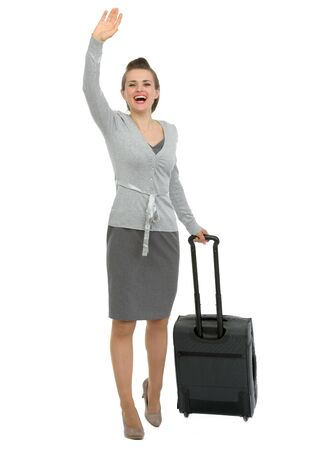 excited business woman: Excited traveling woman with suitcase waving hand