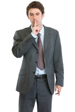 Modern businessman showing shh gesture photo