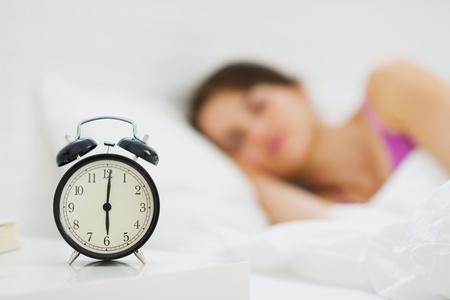 reloj despertador: Alarma en la mesa y la mujer durmiendo en el fondo Foto de archivo