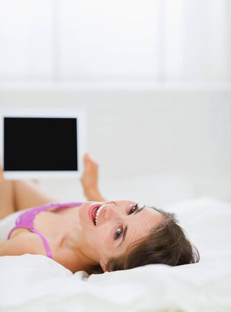 Smiling girl laying in bed and using tablet PC photo
