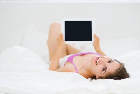 Smiling woman laying in bed and using tablet PC photo