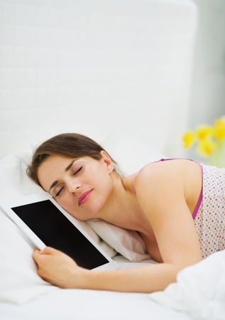 Happy girl sleeping embracing tablet PC photo