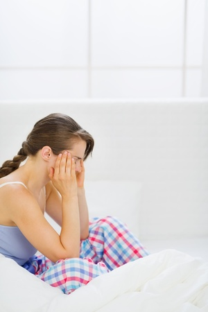 Girl with head ache sitting on bed Stock Photo - 13817625