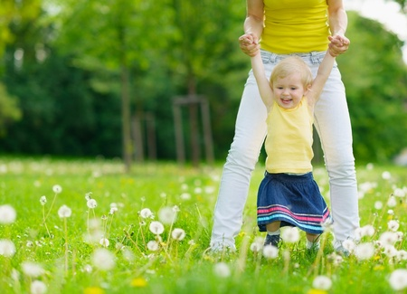 mammy: Mother playing with baby girl on dandelions field Stock Photo