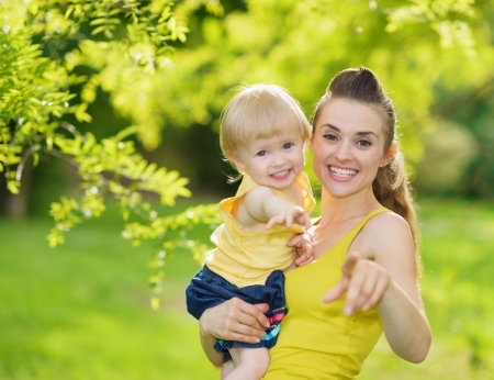 mammy: Portrait of baby girl and smiling mother pointing in camera Stock Photo