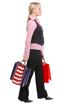 Walking woman with shopping bags. Side view photo
