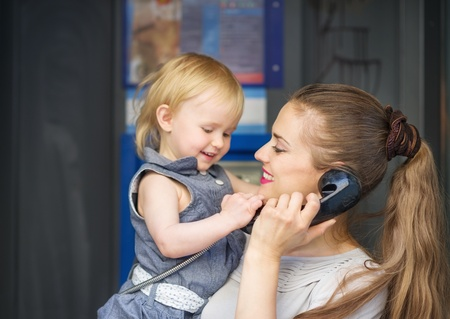 Mother and baby talking phone in city photo