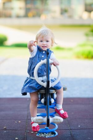 Baby swing on horse on playground and pointing in camera Stock Photo - 14031185