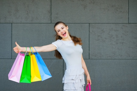 Smiling woman with shopping bags showing thumbs up Stock Photo - 14031180