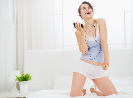 Girl listening music and dancing on bed photo
