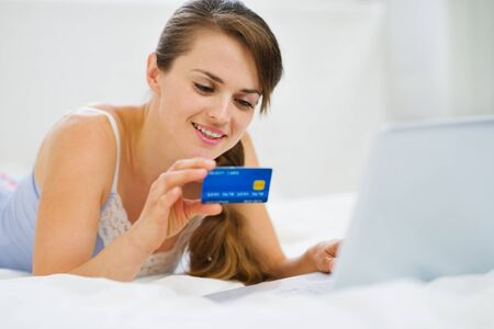 Happy woman laying on bed with laptop and shopping on net photo