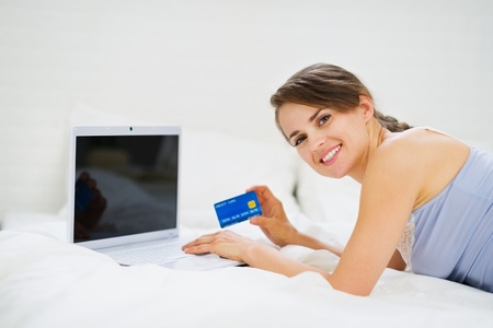 Smiling woman laying on bed with laptop and shopping on net photo