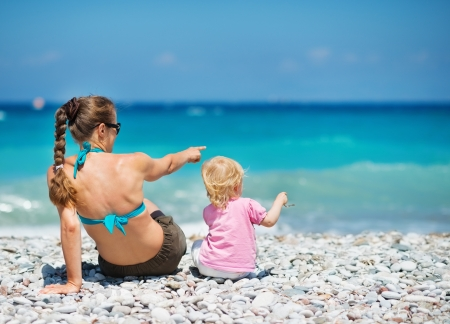 Mother sitting with baby on sea shore and pointing on copy space. Rear view Stock Photo - 14246500