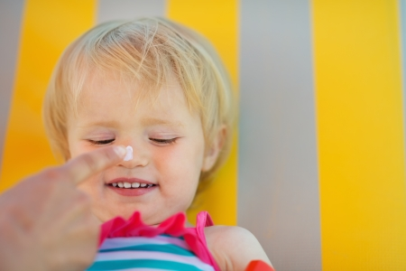 creme: Mothers hand applying sun block creme on baby nose Stock Photo