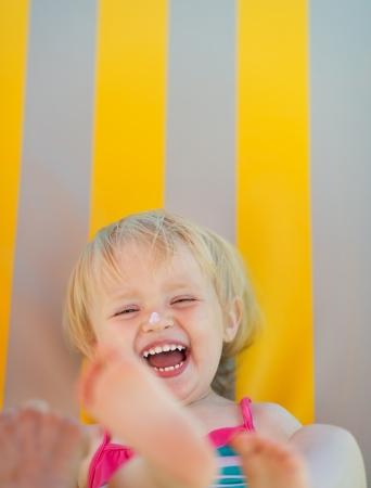 giggle: Retrato de risa beb� con bloqueador solar crema en la nariz