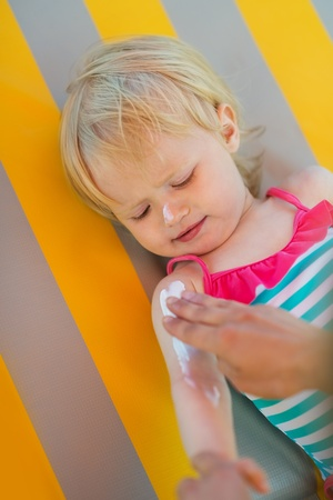 Baby waiting while mother applying sun block creme on arm Stock Photo - 14246496