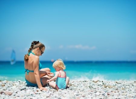 Mother playing with baby on beach. Rear view Stock Photo - 14246462