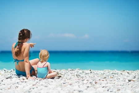 Mother sitting with baby on sea shore looking into distance. Rear view Stock Photo - 14246487