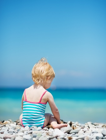 Baby sitting on sea shore. Rear view Stock Photo - 14246492