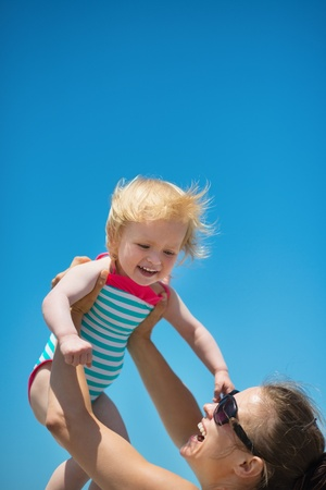 Mother raises baby in air Stock Photo - 14246497