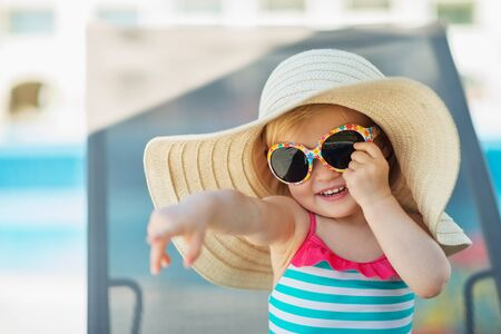 Portrait of baby in hat and glasses pointing in corner Stock Photo - 14246445