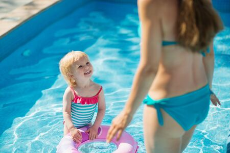 Baby standing in pool with inflatable ring and looking on mother Stock Photo - 14246468