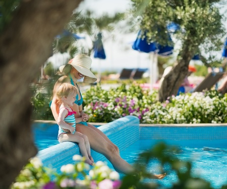 Mother with baby sitting on pool side photo