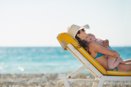 Mother with baby laying on sunbed on beach
