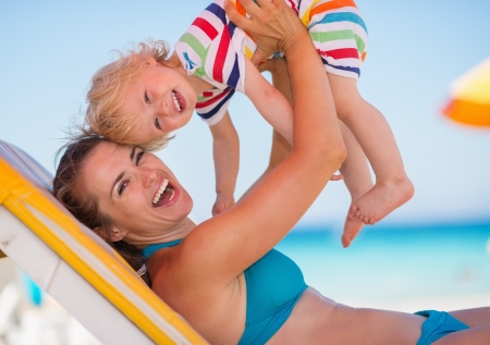 Portrait of mother playing with baby on beach Stock Photo - 14246481