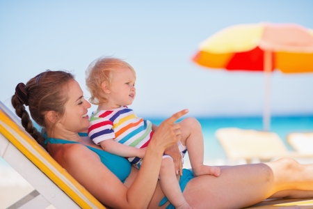 Mother with baby laying on sunbed and pointing on copy space photo
