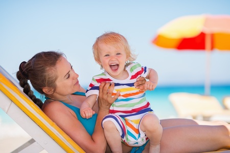 Portrait of excited baby with mother on beach Stock Photo