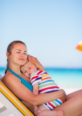 Mother and baby relaxing on sunbed on beach photo