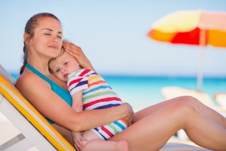 Relaxed mother on sun bed embracing baby Stock Photo - 14246406