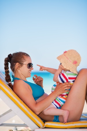 Mother with baby on beach playing with sunglasses Stock Photo - 14246451